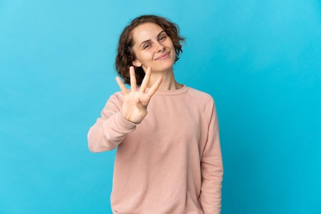Junge englische frau lokalisiert auf blauem hintergrund glücklich und zählt vier mit den fingern