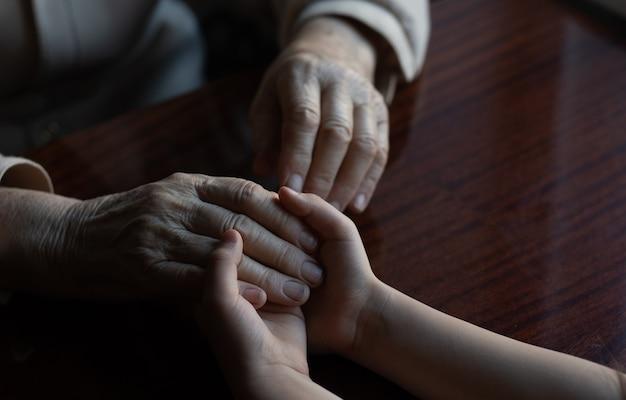 Junge enkelin kümmert sich mit zärtlichkeit und sorgfalt um die großmutter. faltige hände einer sehr alten frau und junge hände einer teenagerfrau aus nächster nähe, der wechsel der familiengeneration. gesundheitswesen und wellness.