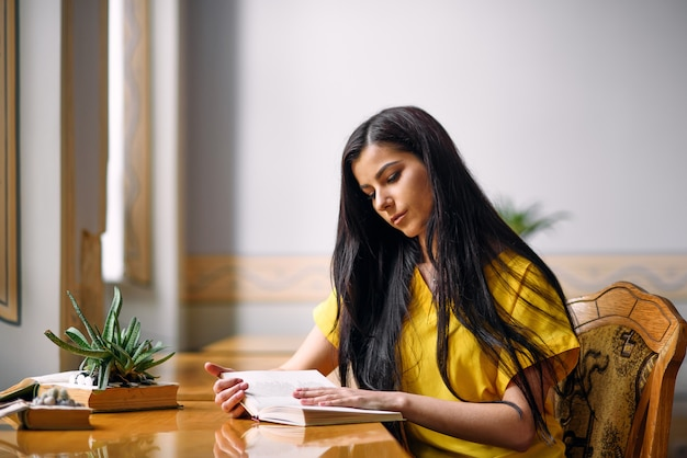 Junge enthusiastische studentenmädchenlesebücher an der alten bibliothek