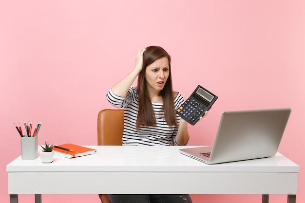 Junge entnervte frau, die sich an den kopf hält, der einen taschenrechner hält, sitzt, arbeitet an einem projekt im büro mit einem modernen pc-laptop einzeln auf pastellrosa hintergrund. erfolgsgeschäftskarrierekonzept. platz kopieren.