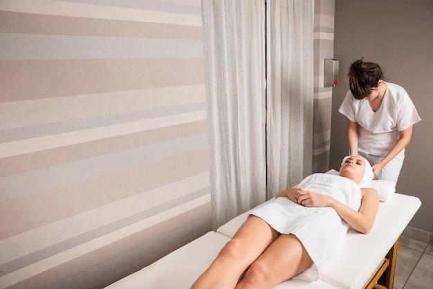 Junge entspannende frau während der kosmetiker, der tuch auf dem kopf der frau am badekurort einwickelt