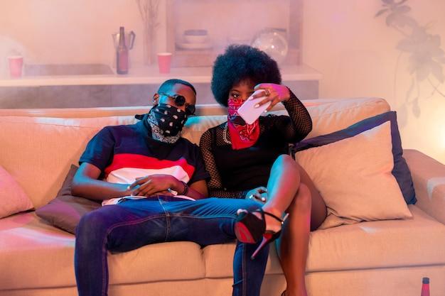 Junge entspannte daten der afrikanischen ethnischen zugehörigkeit machen selfie, während sie auf weicher bequemer couch mit kissen in der häuslichen umgebung sitzen
