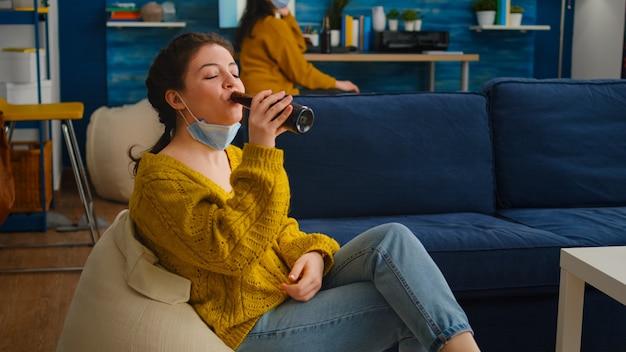 Junge entspannte frau, die gesichtsmaske abnimmt und die kamera anschaut, die bier trinkt und auf der couch sitzt, während sie während der globalen pandemie mit coronavirus zeit mit freunden verbringt. gruppe junger leute, die spaß haben.