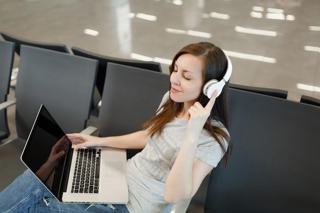 Junge entspannte reisende touristenfrau mit kopfhörern hören musik, die auf laptop mit leerem bildschirm arbeitet, warten in der lobbyhalle am flughafen?