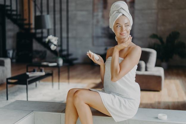 Junge entspannte schöne junge frau mit make-up hat perfekt saubere haut trägt feuchtigkeitscreme auf