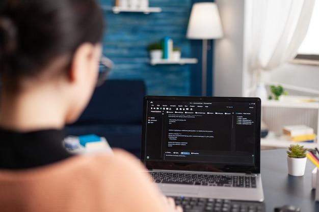 Junge entwickler programmieren software, die html-code-deloping-anwendung für den mobilen einsatz eingibt. student, der an infografiken javascript mit laptop arbeitet, während er am schreibtisch im wohnzimmer sitzt
