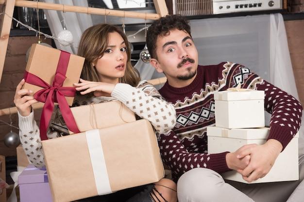 Junge entzückende paare, die auf dem boden sitzen und mit weihnachtsgeschenken aufwerfen.