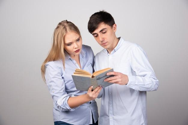 Junge entzückende paare, die interessanten roman auf grauer wand lesen.