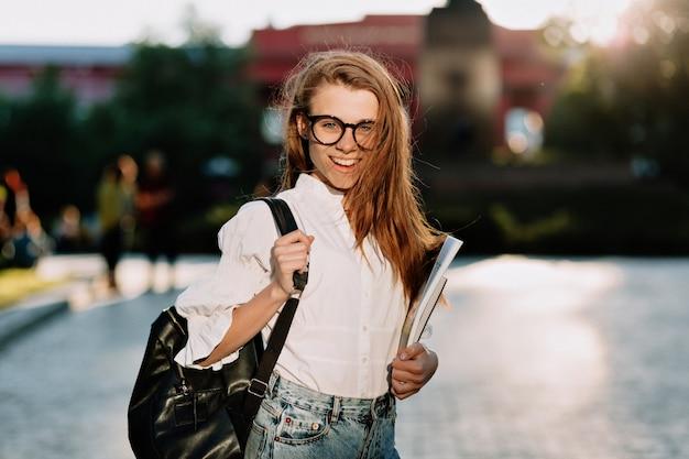 Junge entzückende stilvolle studentin, die weißes hemd und brille trägt