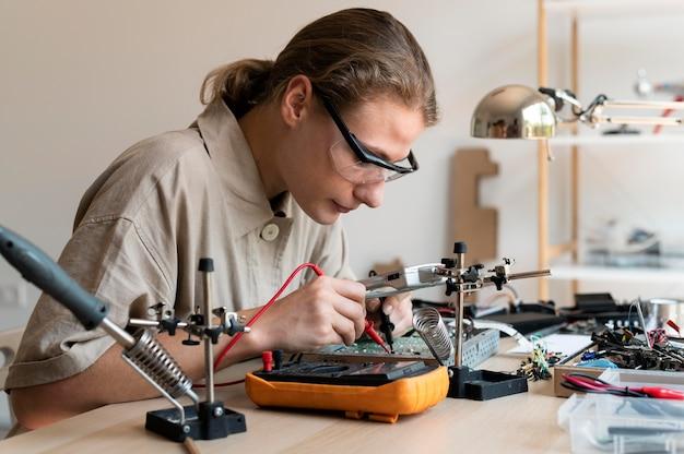 Junge erfinderin, die in ihrer werkstatt kreiert