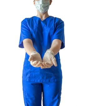 Junge erfolgreiche ärztin in einer blauen medizinischen uniform und einer maske, die leere hände zum helfen zeigt