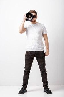 Junge erfolgreiche berufsfotografen im weißen t-shirt verwenden eine digitalkamera mit langer linse. fotograf bereit zu schießen