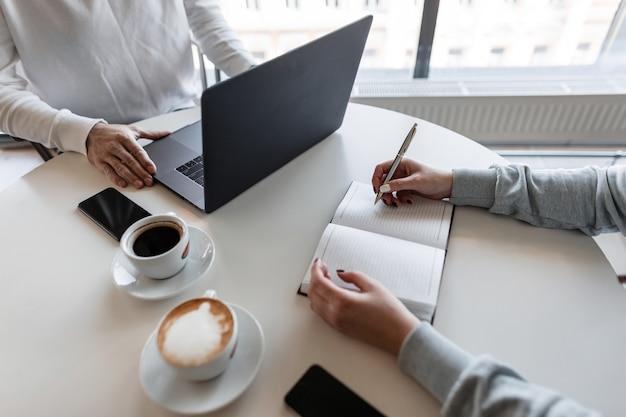 Junge erfolgreiche frau, die am tisch sitzt, der mit einem mannmanager in einem modernen büro zusammenarbeitet