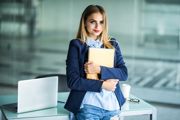 Junge erfolgreiche frau in der freizeitkleidung, die notizbucharbeit steht, die nahe weißem schreibtisch mit laptop im büro steht. erfolgsgeschäft karrierekonzept.