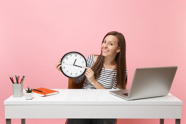 Junge erfolgreiche frau in freizeitkleidung hält runden wecker sitzen am weißen schreibtisch mit zeitgenössischem pc-laptop einzeln auf pastellrosa hintergrund. erfolgsgeschäftskarrierekonzept. platz kopieren.