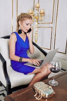 Junge erfolgreiche geschäftsdame im abendkleid, das am telefon spricht und e-mails von kunden beantwortet
