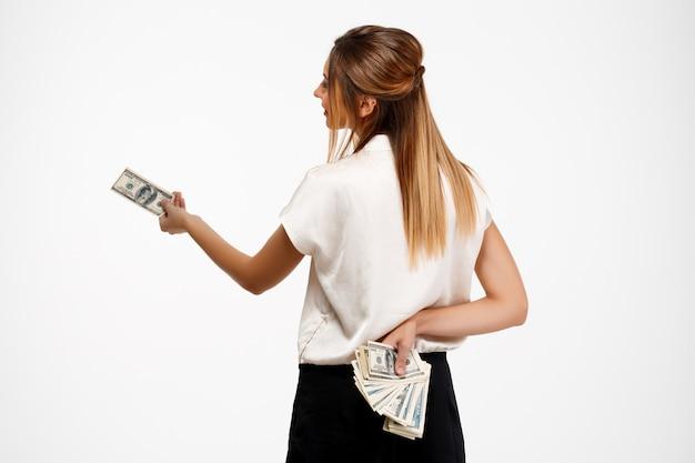 Junge erfolgreiche geschäftsfrau, die geld über weißem hintergrund hält.