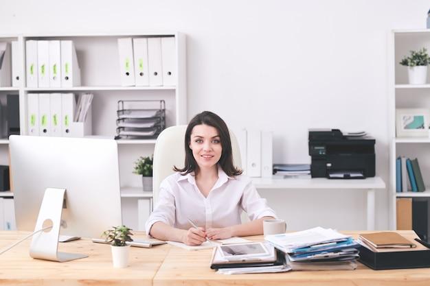 Junge erfolgreiche geschäftsfrau in der abendgarderobe, die vom schreibtisch im büro sitzt und arbeitsplan oder notizen über neues geschäftsprojekt macht