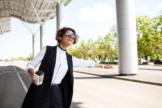 Junge erfolgreiche geschäftsfrau in der sonnenbrille, die auto über geschäftszentrum fängt.