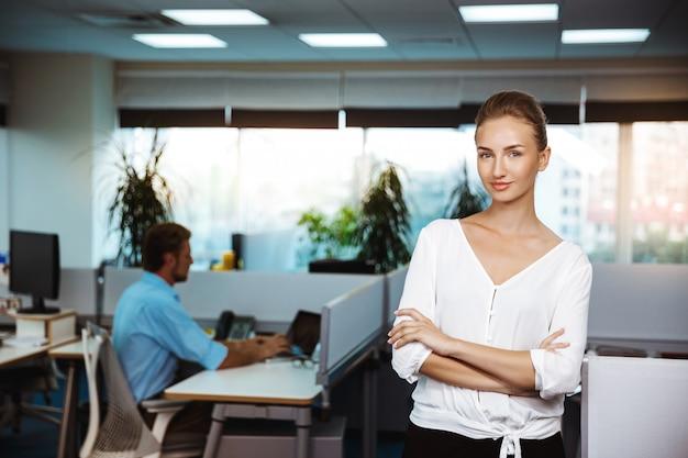 Junge erfolgreiche geschäftsfrau lächelnd, posierend mit verschränkten armen, über büro