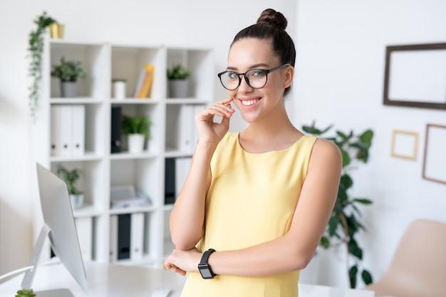 Junge erfolgreiche geschäftsfrau mit dem zahnigen lächeln, das vor kamera mit computermonitor auf hintergrund steht