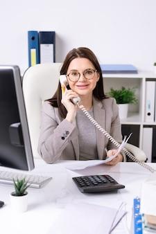 Junge erfolgreiche geschäftsfrau oder buchhalterin in abendgarderobe, die am schreibtisch sitzt und kunden im büro anruft