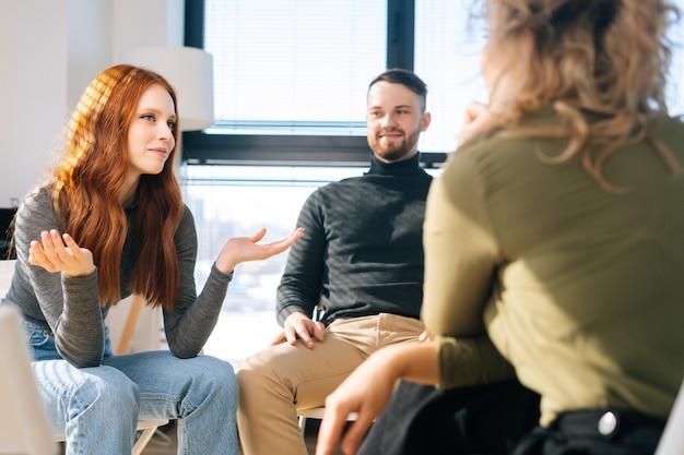 Junge erfolgreiche mitarbeiter sitzen im kreis auf stühlen und diskutieren gemeinsam über arbeits- oder persönliche themen. geschäftsteam, das ein brainstorming-meeting hat, um das ziel im modernen büro zu planen und zu erreichen.