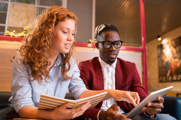Junge erfolgreiche multikulturelle studenten oder angestellte, die auf touchpad-anzeige schauen, während einer von ihnen auf bildschirm zeigt