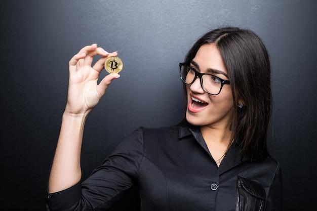 Junge erfolgreiche selbstbewusste frau mit brille hält eine goldene bitcoin in ihrer hand lokalisiert auf schwarzer wand