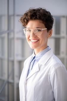 Junge erfolgreiche wissenschaftlerin in weißmantel und brille, die im wissenschaftlichen labor stehen und sie mit zahnigem lächeln betrachten