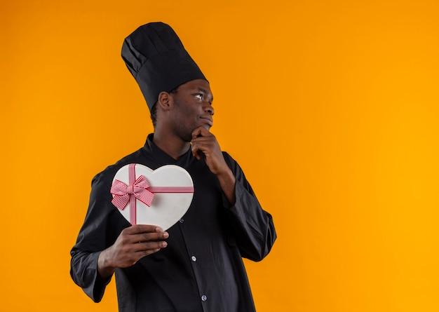 Junge erfreute afroamerikanische köchin in der kochuniform hält herzformbox und legt hand auf kinn auf orange mit kopienraum