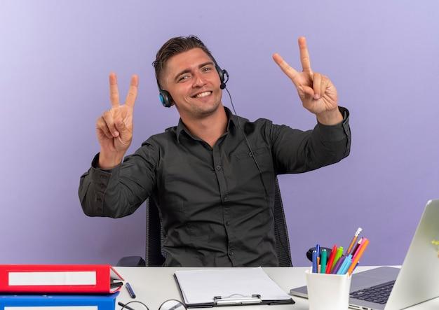 Junge erfreute blonde büroangestellte mann auf kopfhörern sitzt am schreibtisch mit bürowerkzeugen unter verwendung von laptop-gesten siegeshandzeichen lokalisiert auf violettem hintergrund mit kopienraum