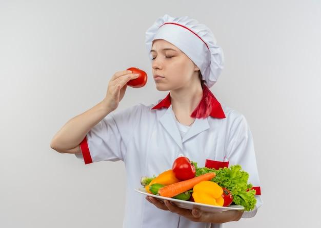 Junge erfreute blonde köchin in kochuniform hält gemüse auf teller und gibt vor, tomaten zu riechen, die auf weißer wand isoliert werden