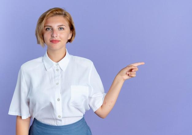 Junge erfreute blonde russische mädchenpunkte an der seite lokalisiert auf lila hintergrund mit kopienraum