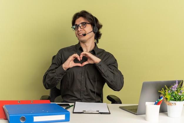 Junge erfreute büroangestellte mann auf kopfhörern in optischen gläsern sitzt am schreibtisch mit bürowerkzeugen unter verwendung von laptop-gesten-herzhandzeichen lokalisiert auf grünem hintergrund mit kopienraum