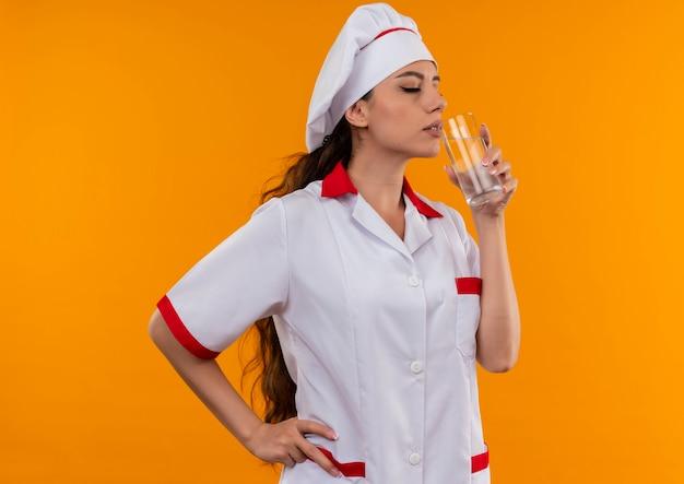 Junge erfreute kaukasische köchin in der kochuniform gibt vor, glas wasser zu trinken, das auf orange wand mit kopienraum isoliert wird
