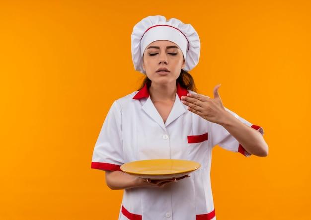 Junge erfreute kaukasische köchin in der kochuniform hält platte und gibt vor, isoliert auf orange wand mit kopienraum zu riechen