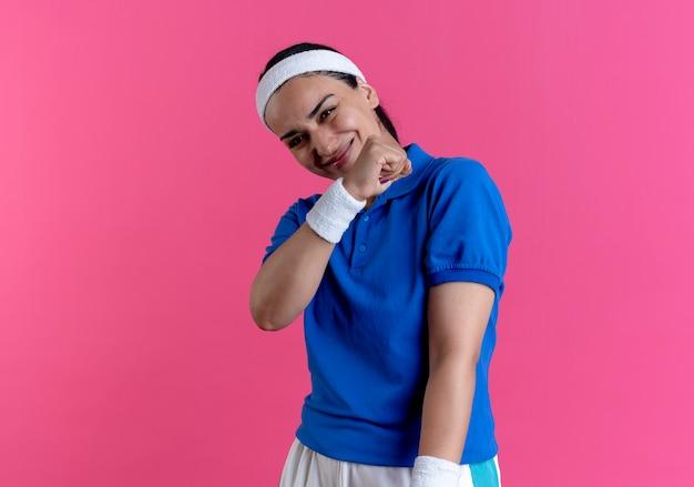 Junge erfreute kaukasische sportliche frau, die stirnband und armbänder trägt, steht mit erhobener faust