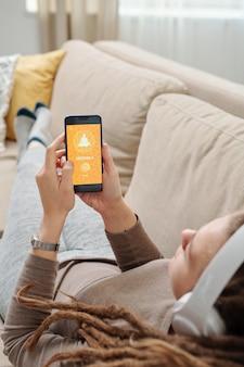 Junge erholsame frau mit smartphone, das auf couch liegt und auf das hochladen der yoga-website-seite wartet