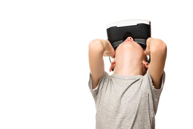 Junge erlebt virtuelle realität und hebt den kopf. auf weißem hintergrund isolieren. technologiekonzept.
