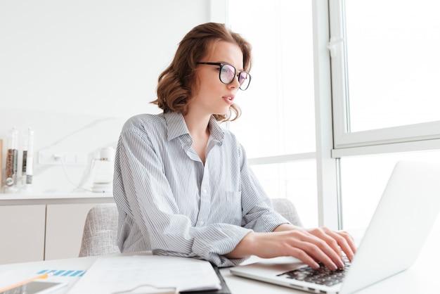 Junge ernste frau im gestreiften hemd, das e-mail an ihren chef beim sitzen am arbeitsplatz in der hellen wohnung schreibt