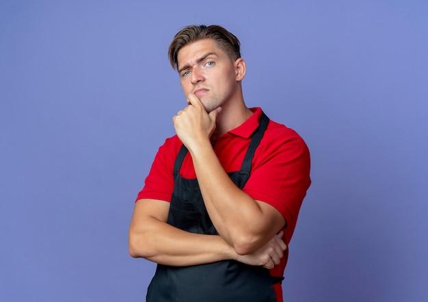 Junge ernsthafte blonde männliche friseur in uniform legt hand auf kinn isoliert auf violettem raum mit kopierraum