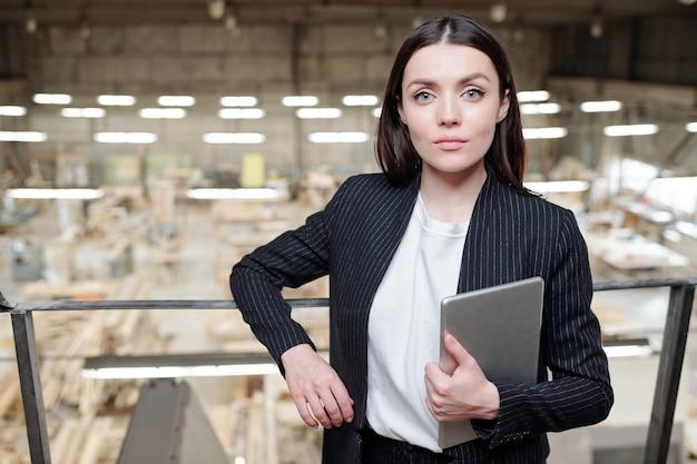 Junge ernsthafte brünette verkaufsleiterin einer modernen möbelfabrik, die vor der kamera steht und dich ansieht
