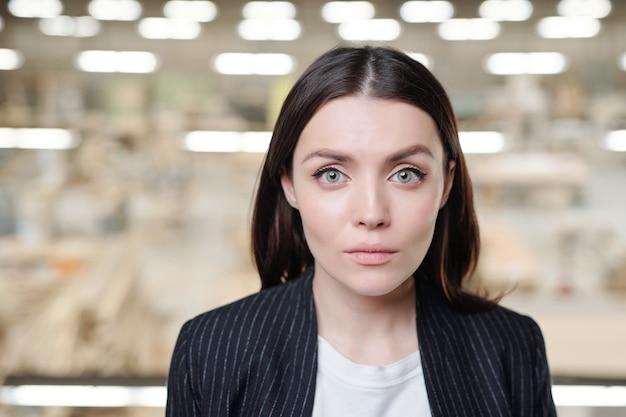 Junge ernsthafte brünette weibliche verkaufsleiterin der zeitgenössischen möbelfabrik, die vorne steht und schaut