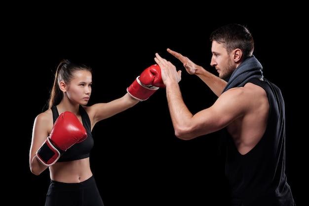 Junge ernsthafte fit frau in aktivkleidung und boxhandschuhen, die trainer während des kampfes schlagen