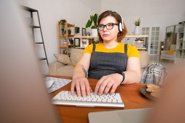 Junge ernsthafte frau mit kopfhörern, die ihre finger auf tastatur halten und daten auf computerbildschirm betrachten, während sie zu hause arbeiten
