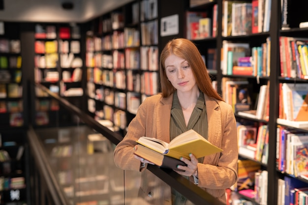 Junge ernsthafte frau mit offenem buch, die es in der bibliothek liest