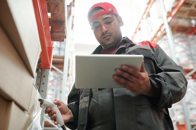 Junge ernsthafte gemischtrassige lagerarbeiterin, die auf das tablet-display schaut, während sie mit verpackten waren am regal steht und qr-codes scannt