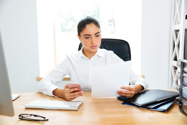 Junge ernsthafte geschäftsfrau, die dokumente betrachtet und das handy hält, während sie im büro sitzt