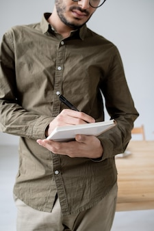 Junge ernsthafte männliche angestellte in der freizeitkleidung, die notizen im notizbuch macht, während arbeit im büro organisiert